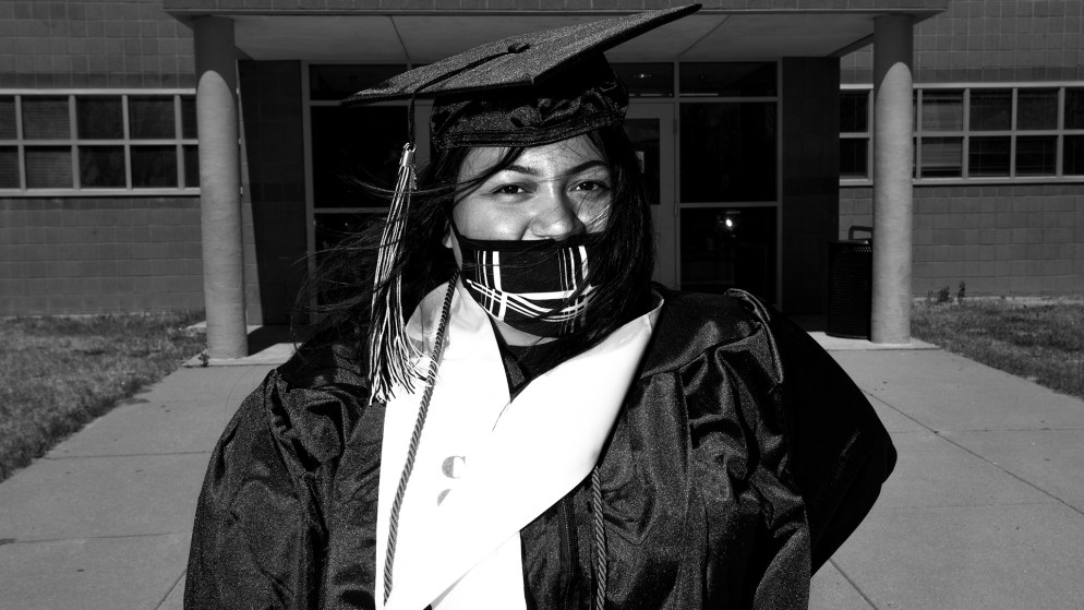 Jennifer Lugo poses for a cap-and-gown picture during a graduation celebration at Martin Luther King Jr. Early College in Green Valley Ranch. May 8, 2020. (Kevin J. Beaty/Denverite)