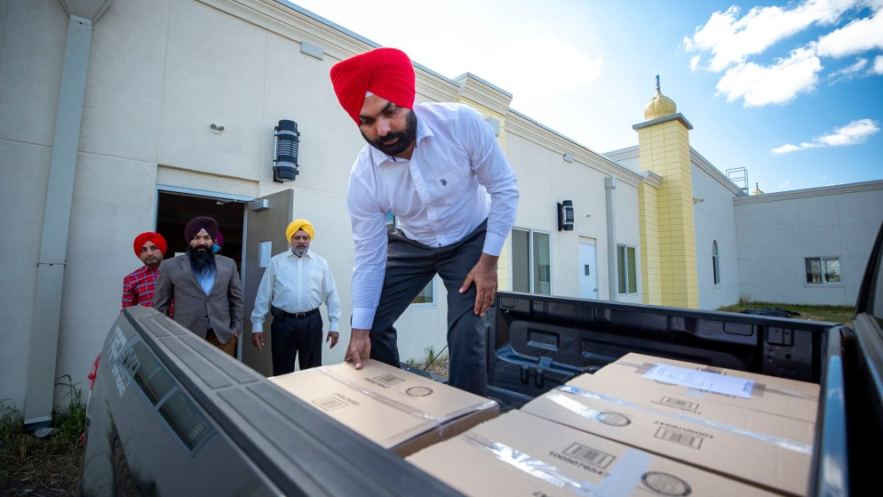 Kanwarbar Sandhu loads boxes of snacks, packed here at Colorado Singh Sabha in Commerce City, into a truck bound for frontline workers across the state. May 8, 2020. (Kevin J. Beaty/Denverite)