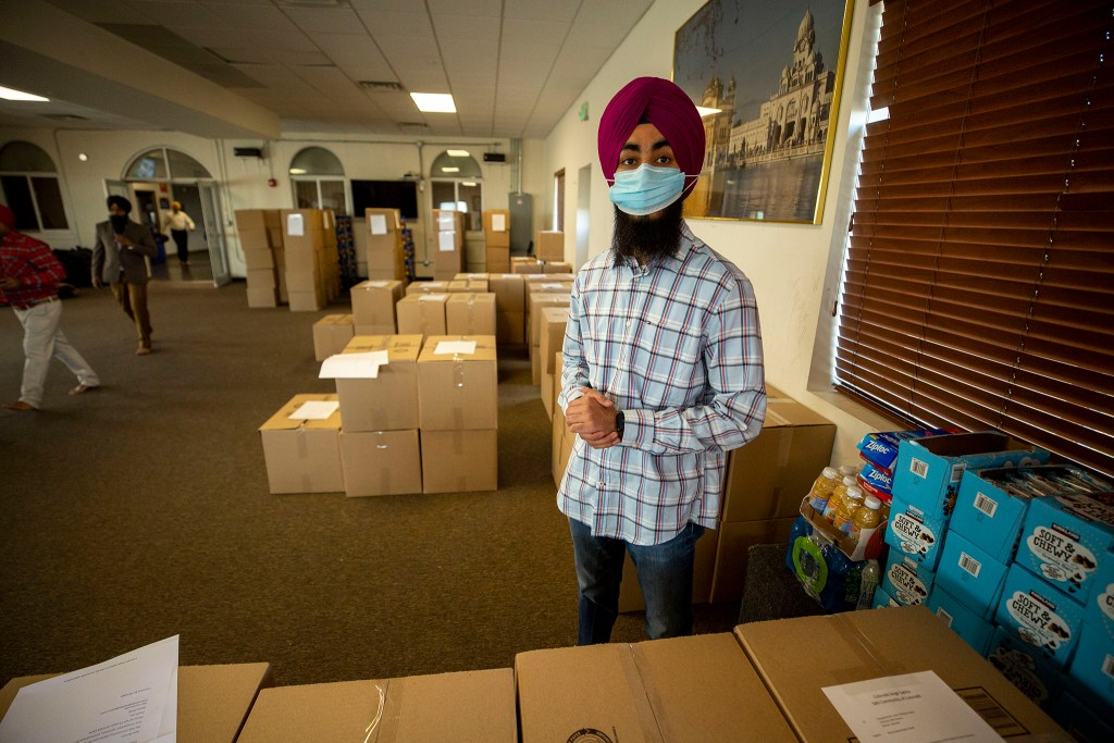Anmol Singh stands among many boxes packed here at Colorado Singh Sabha Commerce City that are bound for frontline workers around the state. May 8, 2020. (Kevin J. Beaty/Denverite)