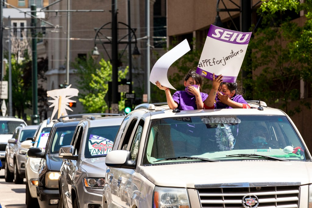 Kids hold signs from a sunroof of a car protesting with Service Employees International Union janitors for better safety measures and higher wages outside of 1801 California Street downtown. May 19, 2020. (Kevin J. Beaty/Denverite)