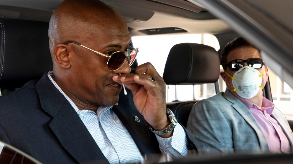 Mayor Michael Hancock's security detail, who declined to be named, sticks a cotton swab into his nose at a new mass testing facility for COVID-19 at the Pepsi Center. May 21, 2020. (Kevin J. Beaty/Denverite)