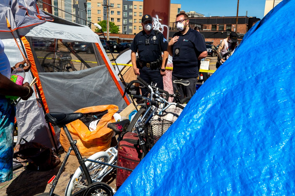 Authorities tell residents of an encampment near the intersection of California and 21st Streets that they must move or else go to jail. May 27, 2020. (Kevin J. Beaty/Denverite)