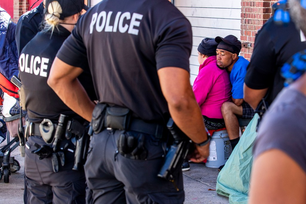 Christopher Johnson leans on his wife, Christina, after authorities instructed the couple to move their camp from the corner of California and 21st Streets. May 27, 2020. (Kevin J. Beaty/Denverite)