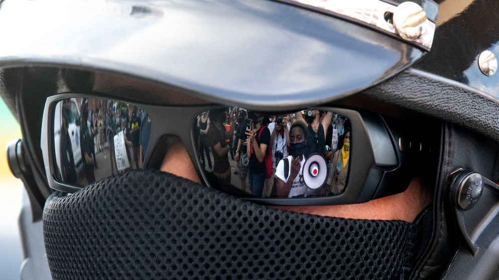 Protest leader Keezy A. seen through the reflection of a Denver Police officer's sunglasses as a march reacting to the death of George Floyd comes face to face with authorities at 20th Street and Chestnut Place. May 28, 2020. (Kevin J. Beaty/Denverite)