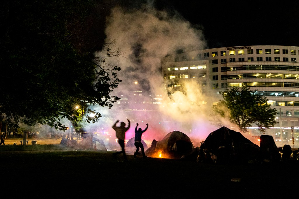 Protesters rush to put out a fire set on an unhoused resident's tent by a Denver Police smoke bomb thrown during a massive reaction to the killing of George Floyd. May 28, 2020. (Kevin J. Beaty/Denverite)