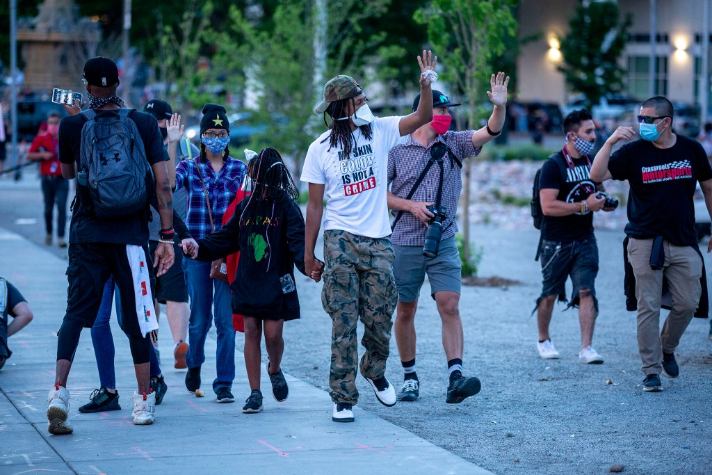 Quincy Shannon walks his daughter between police and agitating protesters after he attempted to keep ralliers from goading officers. May 29, 2020. (Kevin J. Beaty/Denverite)