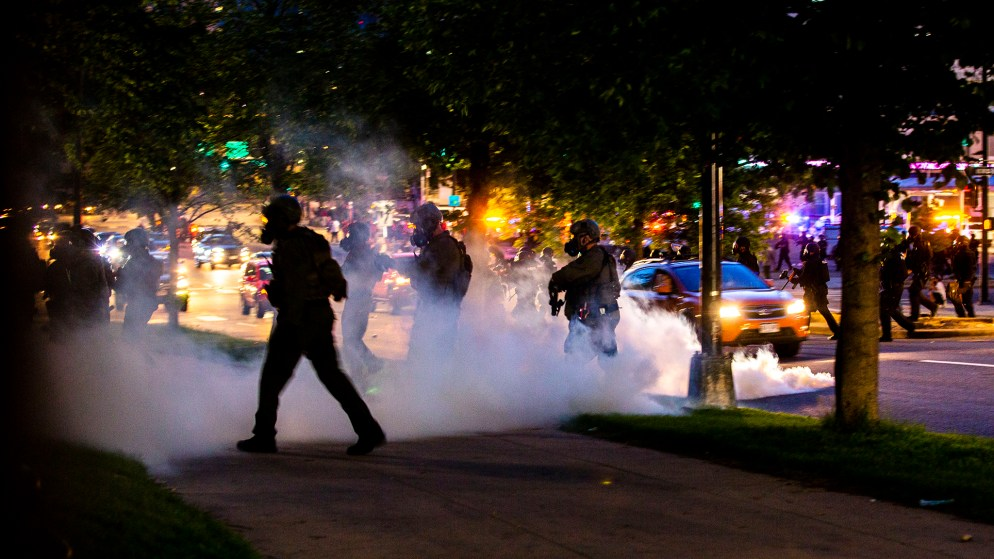 Denver Police officers in riot gear walk onto block around the Capitol as they fill the lawn with tear gas to push protesters away. May 29, 2020. (Kevin J. Beaty/Denverite)