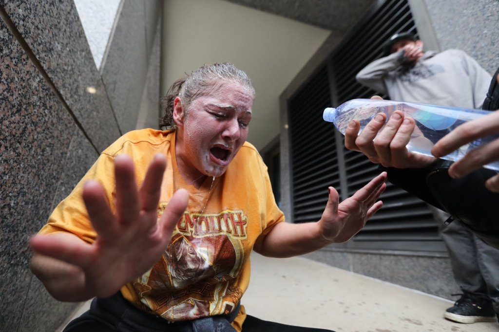 A protester washes her face with milk after being teargassed. Protesters filled the lawn in front of the Colorado Capitol building on May 30, 2020, to protest the death of George Floyd in Minneapolis police custody.