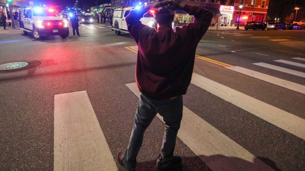 A man observes police activity at Colfax Avenue and Logan Street during protests against the death of George Floyd on Thursday, May 28, 2018. (Hart Van Denburg/CPR News)