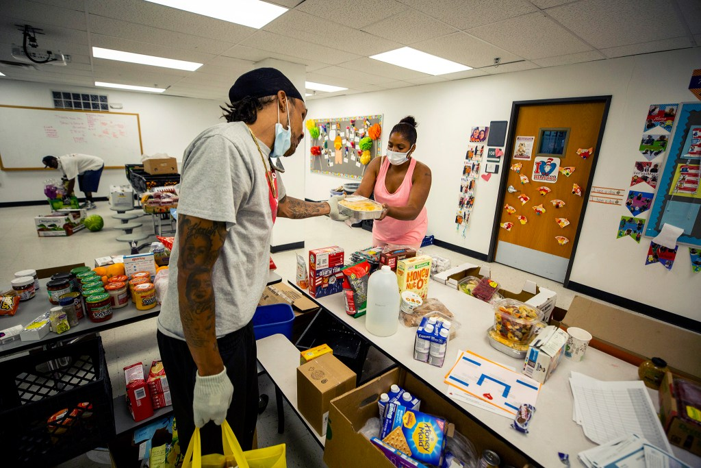 Tae Neal and Joel Hodge work at the Struggle of Love Foundation's food pantry in Montbello. May 6, 2020. (Kevin J. Beaty/Denverite)