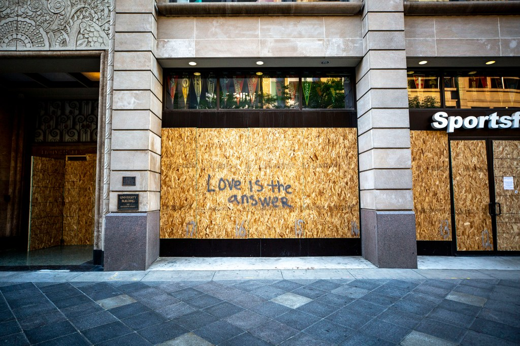 """""""Love is the answer"""" painted on plywood covering a 16th Street Mall business. June 2, 2020. (Kevin J. Beaty/Denverite)"""