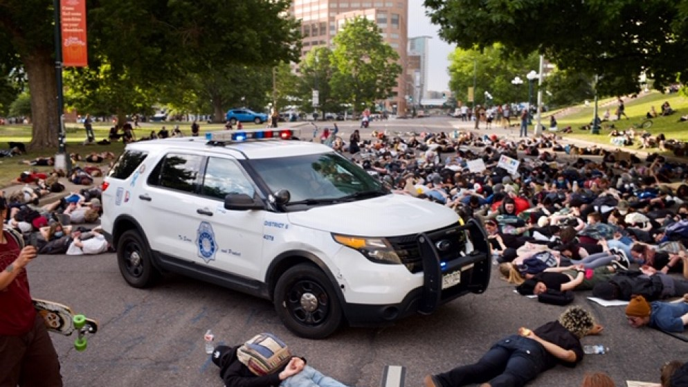 Protesters lie face down around a Denver Police Department SUV in the middle of Lincoln Street on Monday, June 8, 2020. (Carl Glenn Payne/For Denverite)