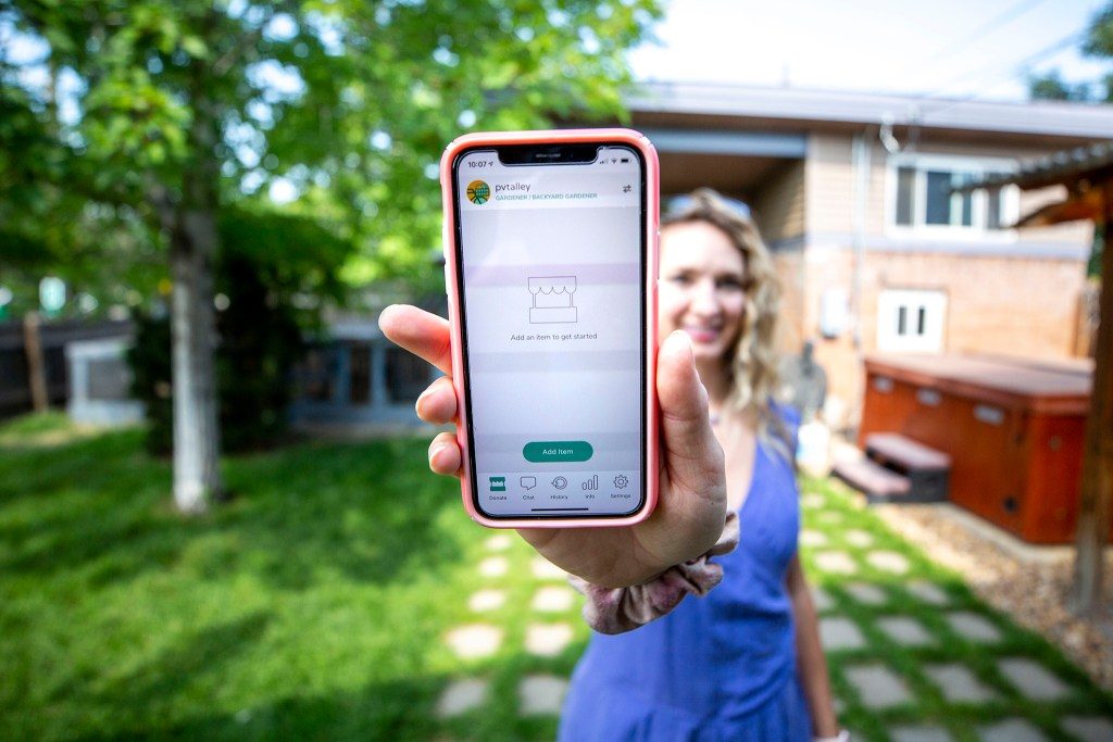 Pamela Talley holds up the Fresh Food Connect app she uses to donate veggies from her backyard garden here in Denver's Clayton neighborhood. July 21, 2020.