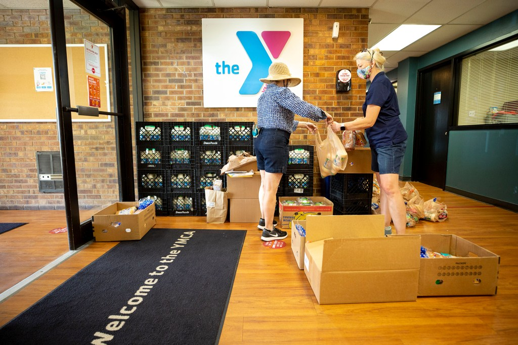 Lydia Raber and Rhonda Harshbarger pack bags of food at the Southwest Family YMCA. July 24, 2020.