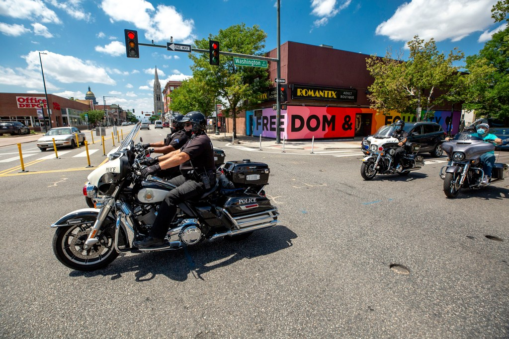 Denver Police officers drive across Colfax Avenue in Capitol Hill. July 30, 2020.