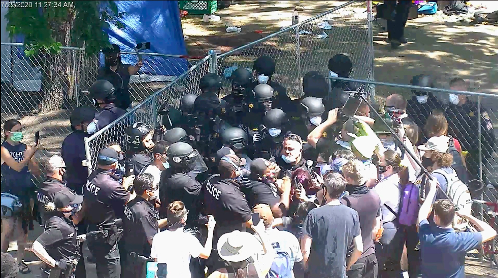 A still from the HALO footage showing Tay Anderson, at the center with the backwards baseball cap, as he falls after being pushed by police.