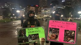 """Self-styled """"defenders"""" hold up illustrated shields before a late night protest in Denver, August 28, 2020."""