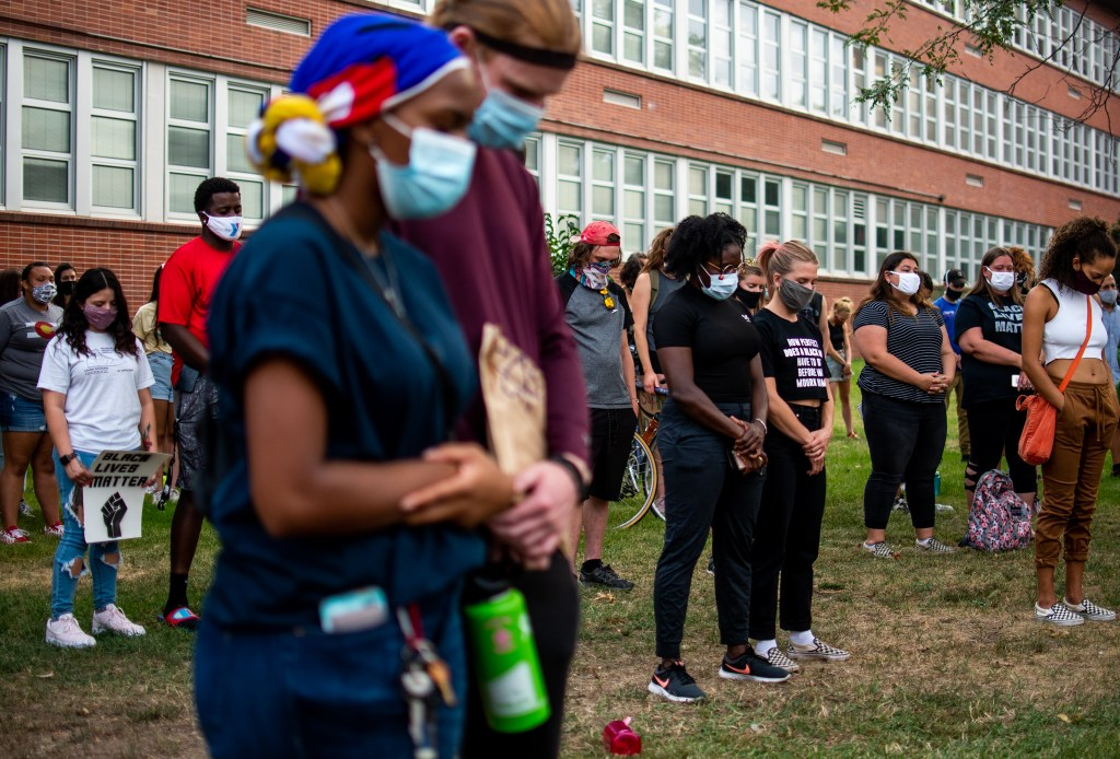 "Attendees bow their heads in prayer for Jacob Blake and victims of police brutality during the ""Protect Black Men: Colorado Action for Jacob Blake"" gathering at Manual High School in Denver."
