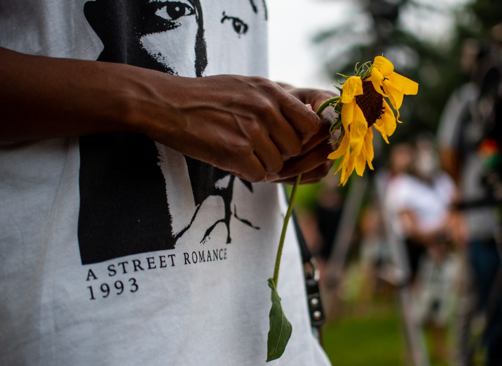 "Sheree Barbour holds a flower during the ""Protect Black Men: Colorado Action for Jacob Blake"" gathering at Manual High School in Denver."