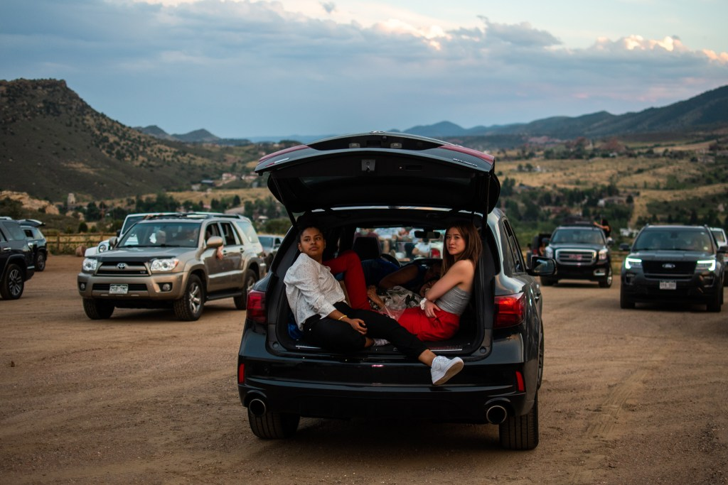 Soraya Serrano, left, and Clover Duhart watch Grease in their trunk during the 21st annual Film on the Rocks, drive-in edition at Red Rocks Park on Aug. 13, 2020.