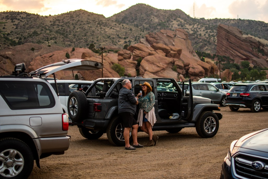 Jeff Hassemer and Christine Kennedy talk as the sun sets over Red Rocks before Grease kicks off the 21st annual Film on the Rocks, drive-in edition on Aug. 13, 2020.