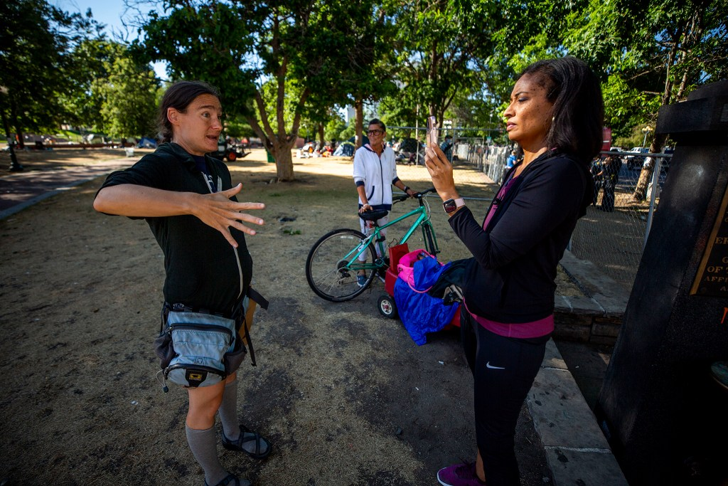 Lisa Calderón (right) interviews Denver Homeless Out Loud's Terese Howard as city officials conduct a forced cleanup of encampments at Lincoln Park, across Lincoln Street from the Capitol. July 29, 2020.