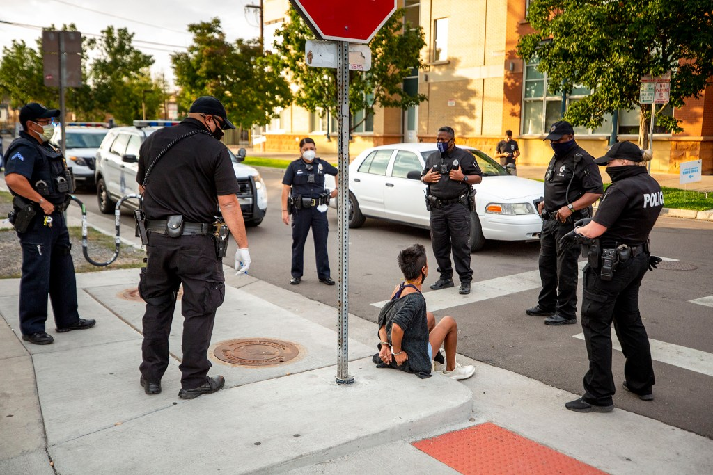 Police surround Blanca Martinez after an altercation between her and neighbors while she moved her belongings from a forced cleanup of encampments along Arapahoe Street in Five Points. Sept. 22, 2020.