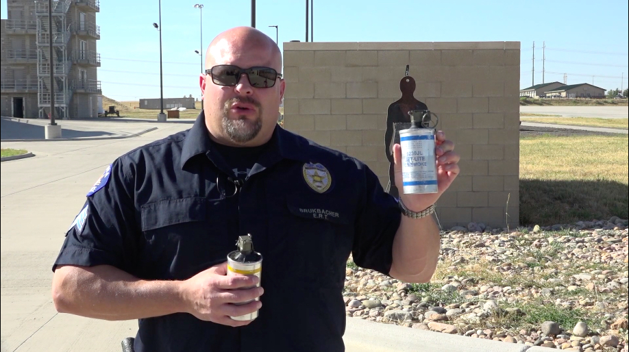 Aurora police Sgt. Matt Brukbacher holds up a tear gas canister during a video demonstrating the department's less-than-lethal means. (Screengrab from YouTube)