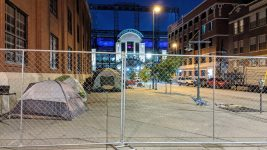 Chain-link fencing was erected before dawn near Coors Field Sep. 29 at the start of a clean-up by Denver's Department of Transportation & Infrastructure. DOTI says such cleanups, which are disruptive and stressful for people experiencing homelessness, are necessary to maintain the public right of way. (Donna Bryson/Denverite)