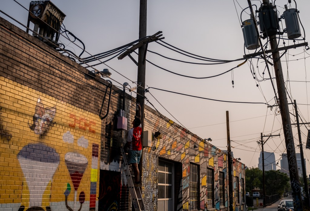 """Crudoe spray paints what he described as """"death phonk"""" on his section of wall in a River North Art District alleyway on Sept. 17, 2020."""