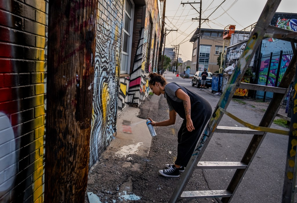 Margarita paints her section of wall in a River North Art District alleyway on Sept. 17, 2020.
