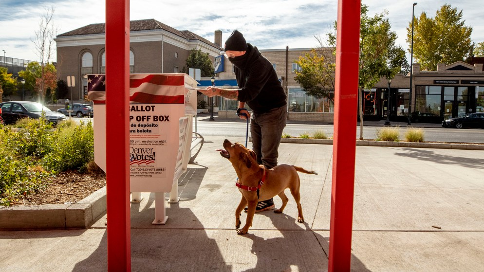 Hank Murphy and Deedee cast a ballot for the November, 2020 election outside of the Carla Madison Rec Center on Colfax Avenue. Oct. 16, 2020.