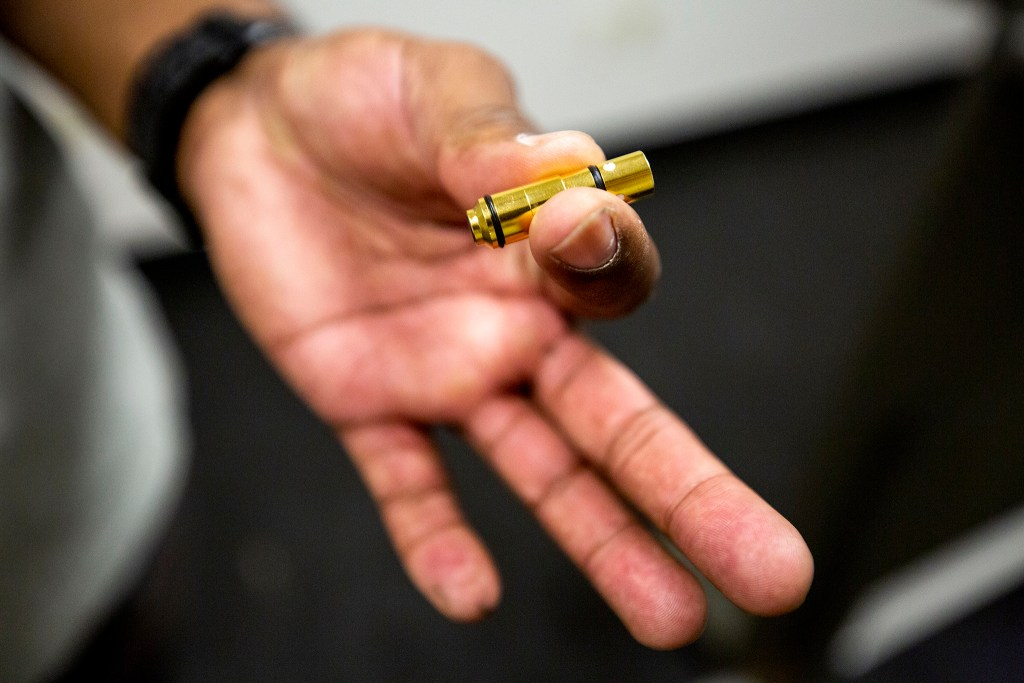 "Instructor Anubis Heru holds one of the infrared 9 millimeter cartridges he uses at 17 Seventy Armory and Gun Club's ""virtual"" gun range in Five Points. Oct. 17, 2020."