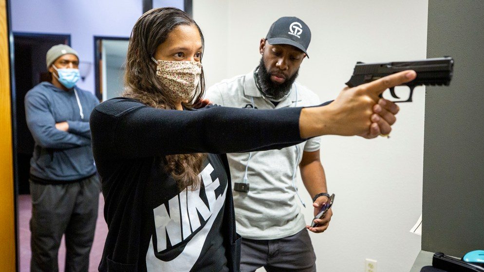 """Instructor Anubis Heru works with Ikaika Hill inside 17 Seventy Armory and Gun Club's new """"virtual"""" range in Five Points. Oct. 17, 2020."""