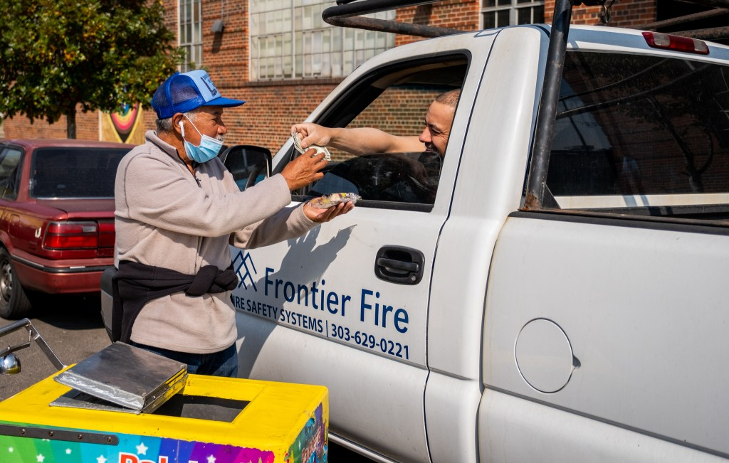 Delgado makes a sale and shares a laugh with a man taking a break from work in his truck in RiNo on Oct. 8, 2020. Each popsicle costs $2, which he splits 50/50 with the paletería, but he often gets tips from people, which significantly increase his income.