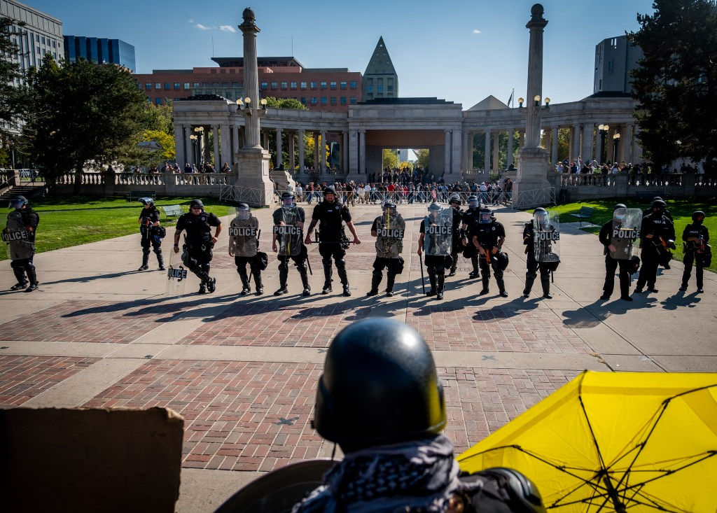 """Police officers stand between a soup drive and """"anti-fascist"""" protest and a """"patriot"""" rally in support of police on October 10, 2020 at Civic Center Park."""