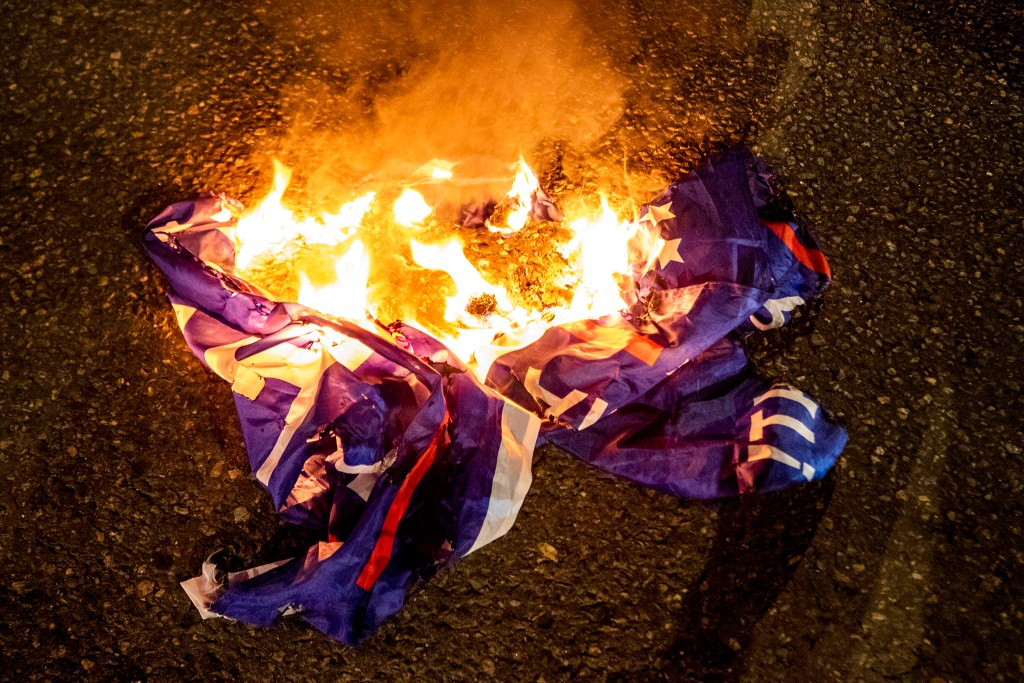Demonstrators protesting the police and the government, regardless of who wins the election, begin their evening on East Colfax Avenue by burning a Trump campaign flag. Nov. 4, 2020.