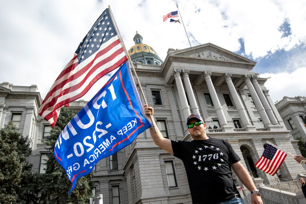 Justin Jacobson waves a flag for President Donald Trump as others celebrate Joe Biden's presidential victory in front of the Colorado State Capitol. Nov. 7, 2020.