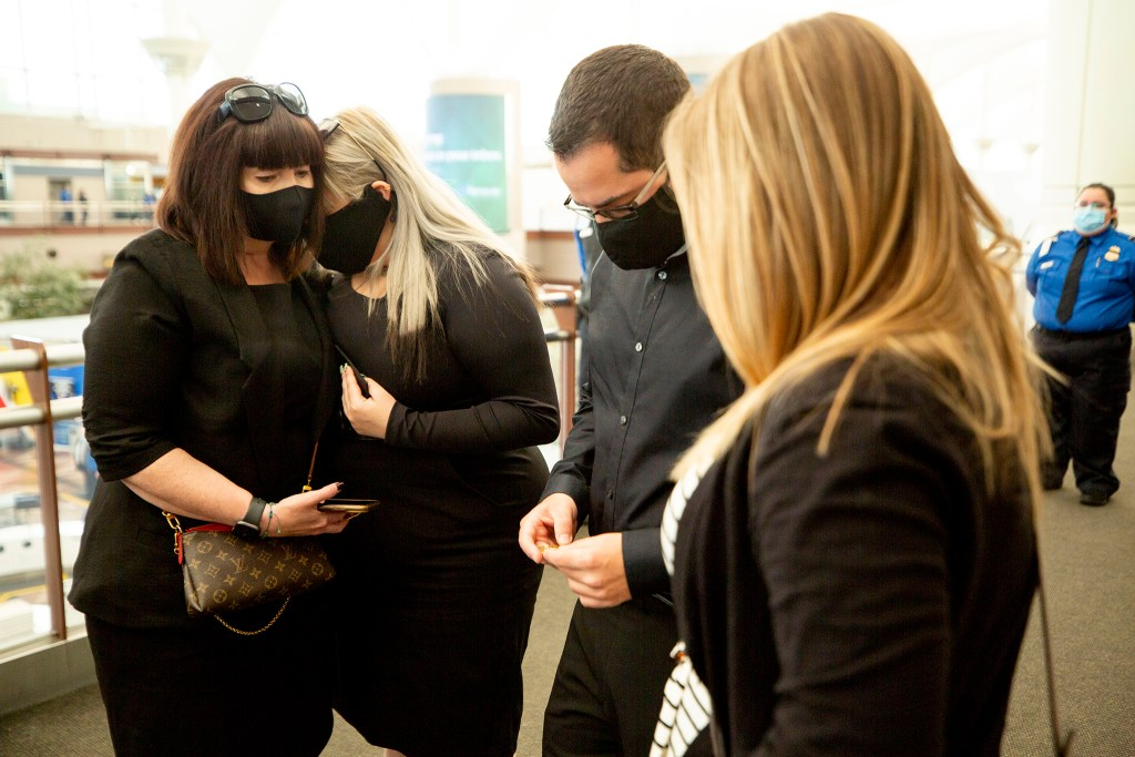 Lana (left to right), Megan and David Faktorovich and Ashley Moore mourn the death of Eduard Faktorovich, a TSA agent who died after contracting COVID-19. Nov, 21, 2020.