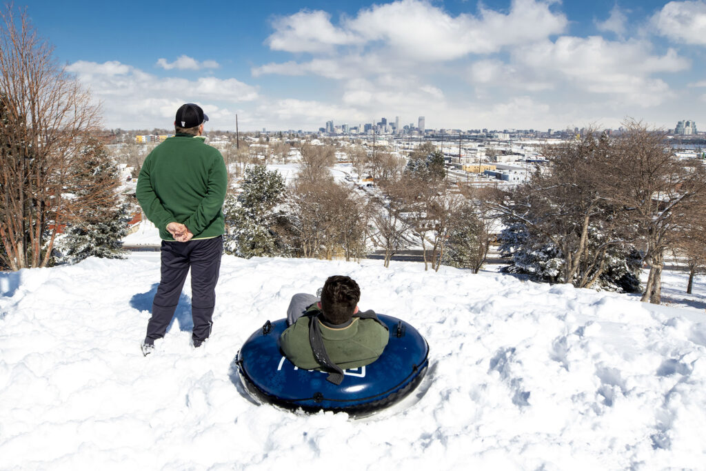 Greg and Grayson Goodman take a break from Ruby Hill in Denver to look out over the city.  February 25, 2021.