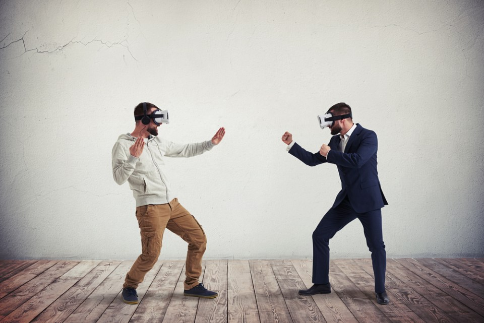 Two men wearing virtual reality glasses in mock hand to hand combat.