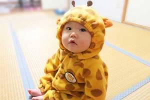 キリンの着ぐるみを着たかわいい赤ちゃんの画像