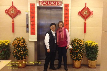 "Vivian poses with our very friendly morning ""Bao An"" (security guard), in front of the New Year decorations in our apartment lobby."