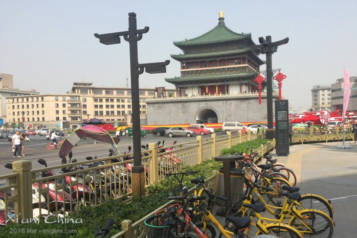"""The Bell Tower has been in the center of Xi'an for centuries, witnessing many changes in modes of transportation. On my first visit (1985), private cares were very rare in China--not so anymore! When I lived here (2002-05), everyone peddled a bike; these have been replaced by mopeds. The newest trend is """"rental bikes"""" (foreground) which can be unlocked using WeChat Pay (social media), and then left anywhere, once the renter is finished with them."""