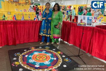 India Folk Artist Jugnu Verma poses with her daughter, behind the sand-art she created for the Columbia International Festival