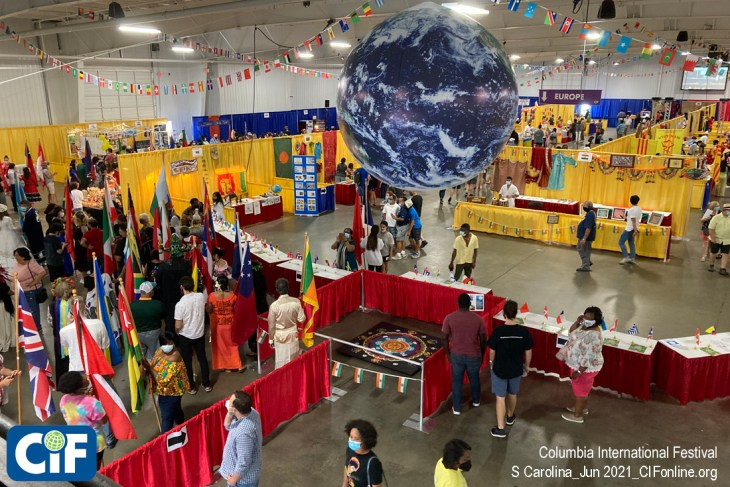 The Columbia International Festival main exhibition hall at the State Fairgrounds, June 5&6 2021. On the left, participants line-up to walk in the popular Parade of Nations. In the center, original floor-art by Indian Folk Artist Jugnu Vermu, under a 10' globe added this year to celebrate the Festival's 25th anniversary.