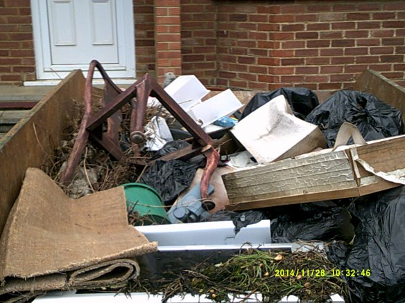 metal skip containing houshold goods including black bin bags, casrpets, brocken chair
