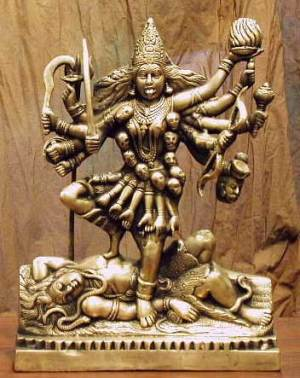 """Statues of Kali, often seen at burial sites, portray a black woman with four arms. In each hand she holds a scimitar, a demon's head, a """"blessings,"""" and either a spear or trident. She always wears a necklace of skulls and earrings of demon heads. Blood also streams from her tongue onto her body. Around her waist is a skirt made of hands."""