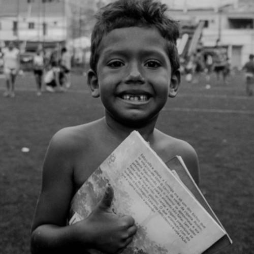Em ação da Bienal da Quebrada, criança recebe livros/Reprodução