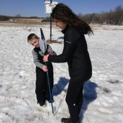 Young boy stands in the snow while teaching a female St. Olaf student how to hold an atlatl.